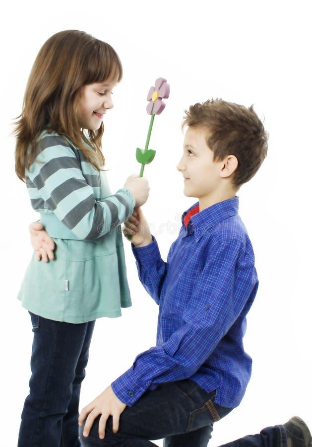 Überraschendes Mädchen des Jungen mit Blumen lizenzfreie stockbilder