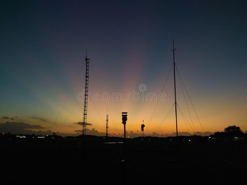 ?berraschendes orange Morgenlicht im blauen Himmel mit Kommunikationsantenne als Schattenbild stockfoto
