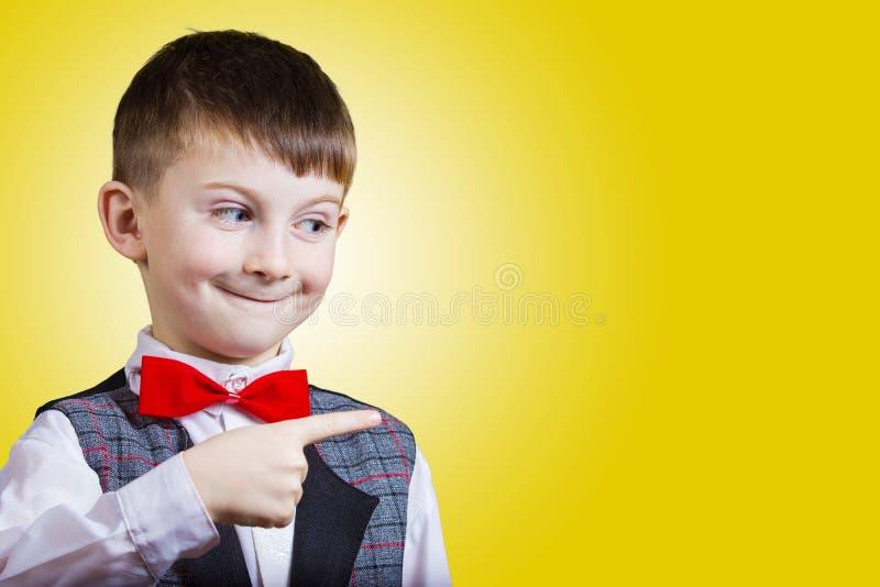 Überrascht, den kleinen Jungen zeigend lokalisiert über gelbem Hintergrund stockfotos
