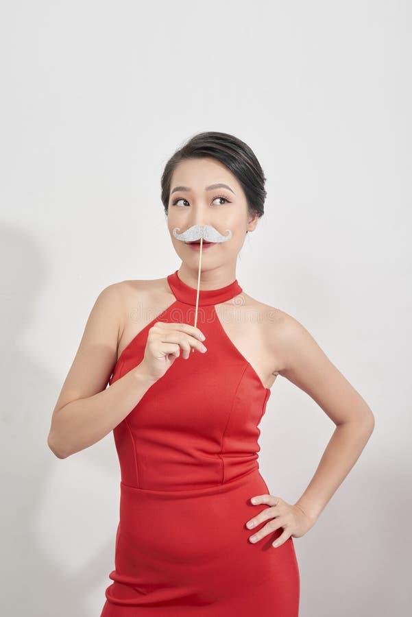 Überrascht, vorbildliches Girl blinzelnd, das lustigen Schnurrbart auf Stock über weißem Hintergrund hält lizenzfreies stockbild