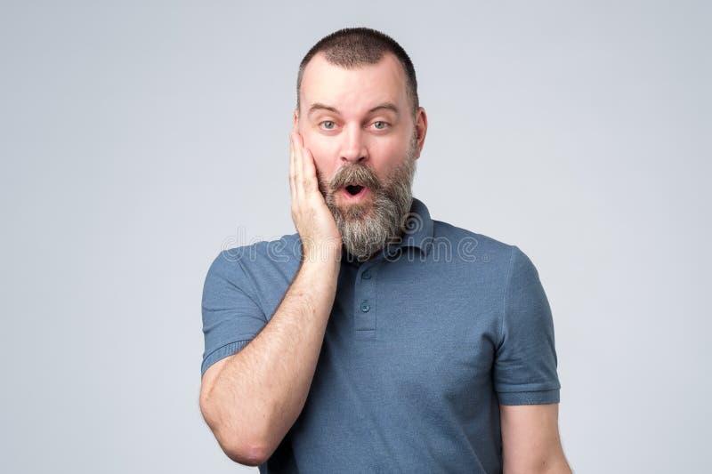 Überraschte bärtige Mannstellung mit offenem Mund stockbilder