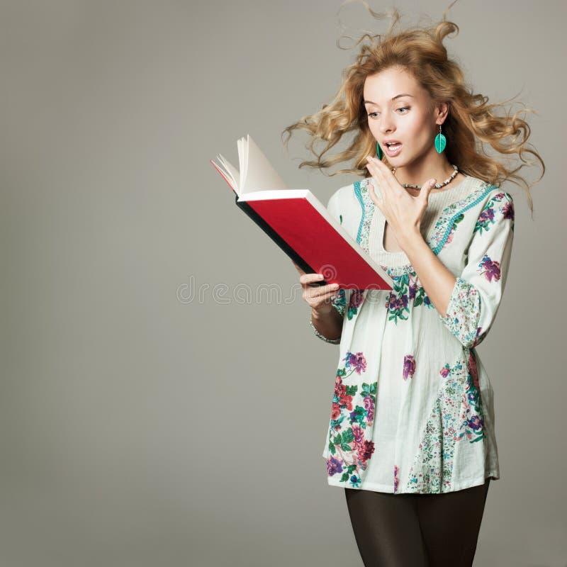 Überraschte blonde Frau, die ein Buch liest lizenzfreie stockfotos