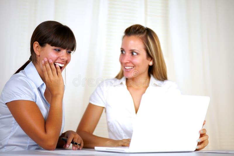 Überraschte erwachsene Geschäftsfrauen, die zusammenarbeiten stockbild