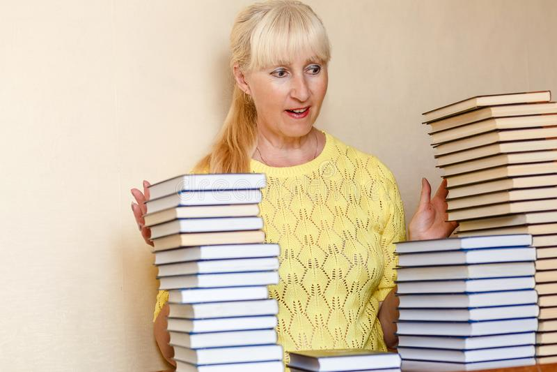 Überraschte fünfzigjährige Frau in einer gelben Strickjacke und in vielen Büchern stockbilder