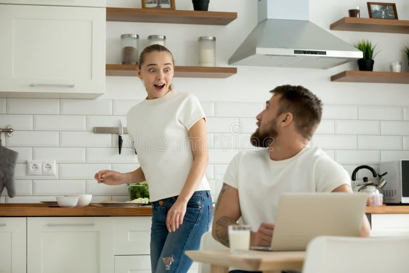 Überraschte Frau aufgeregt, um Nachrichten vom Ehemann in der Küche zu hören lizenzfreie stockbilder