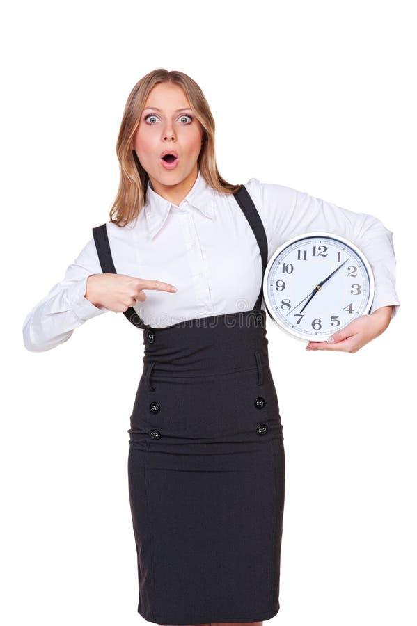Überraschte Frau, die auf die Borduhr zeigt