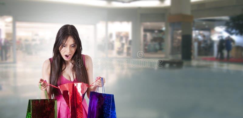 Überraschte Frau, die das Einkaufen betrachtet stockbild