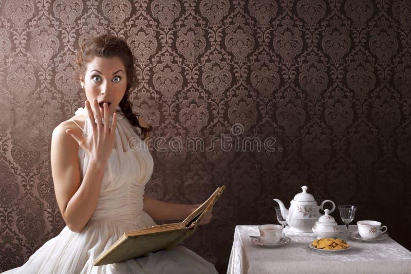 Überraschte Frau, die ein Buch zur Teezeit liest stockfoto
