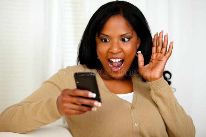 Überraschte Frau, die eine Meldung liest lizenzfreie stockfotografie