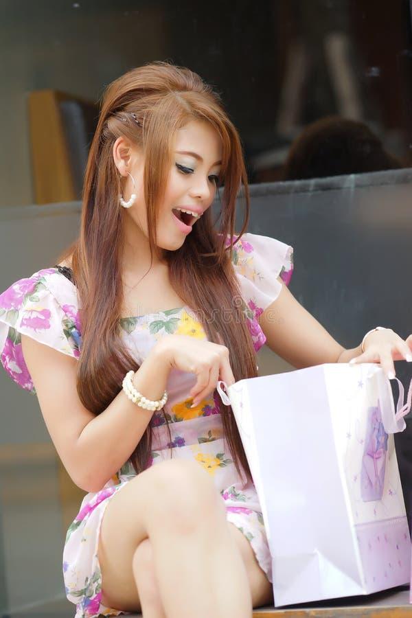 Überraschte Frau, die in einer Einkaufstasche schaut lizenzfreie stockfotos