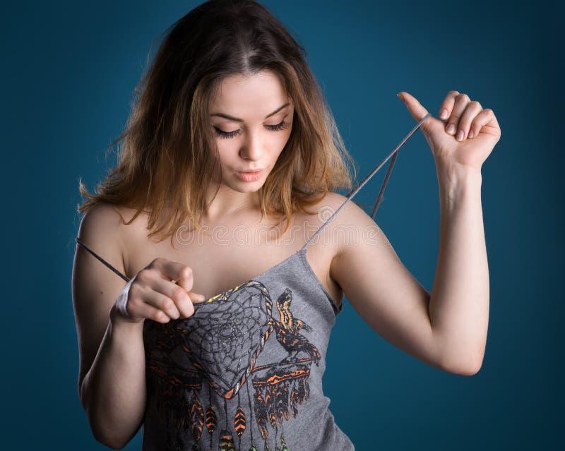 Überraschte Frau, die ihre Brust betrachtet stockfotos