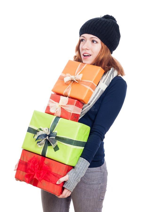 Überraschte Frau, die viele Geschenke trägt lizenzfreie stockbilder