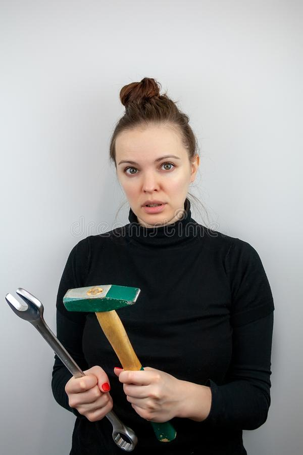 Überraschte Frau mit dem gebündelten Haar und schwarzen der Strickjacke, die einen Hammer und einen großen Schlüssel in ihren Hän lizenzfreies stockfoto