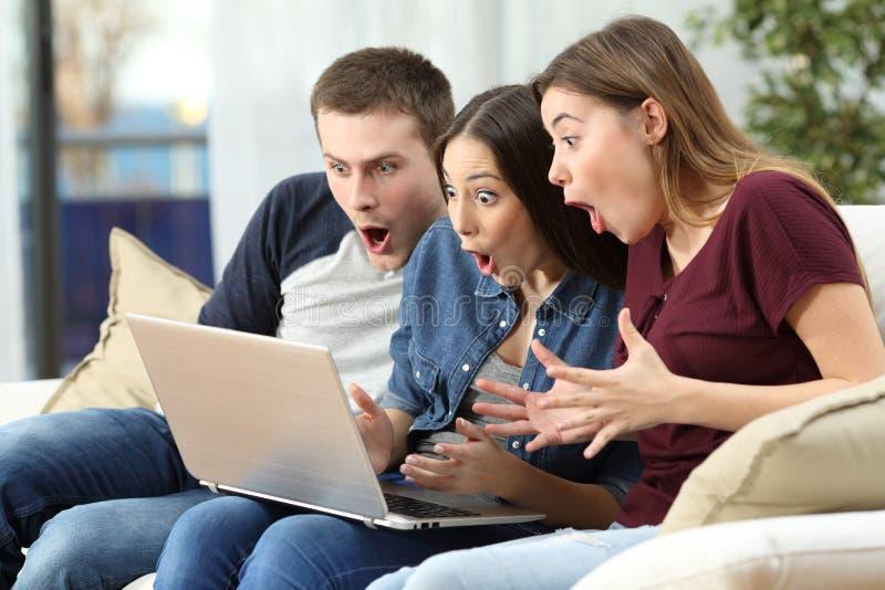 Überraschte Freunde, die Inhalt auf Linie in einem Computer aufpassen lizenzfreie stockfotografie
