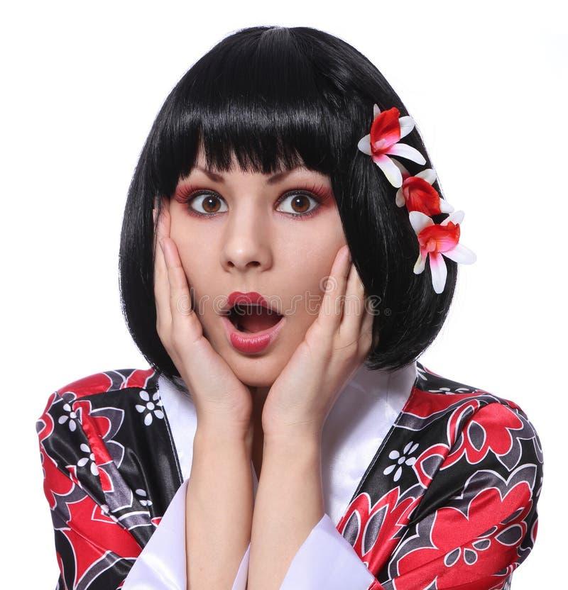 Überraschte Geisha, Porträt der jungen Frau im Kimono und schöne Blumen in ihrem schwarzen kurzen Haar lokalisiert auf Weiß stockbilder