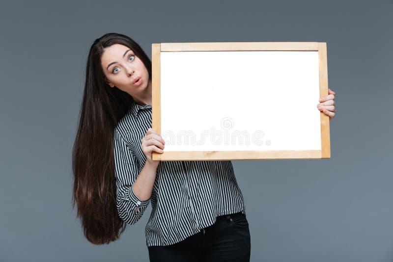 Überraschte Geschäftsfrau, die leeres Brett hält stockfoto