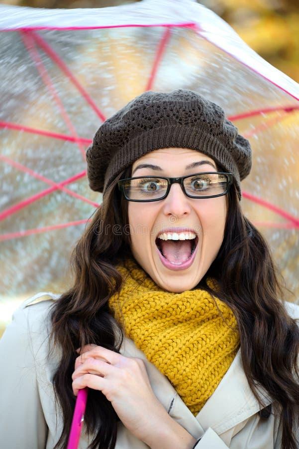 Überraschte glückliche Frau im Herbst mit Regenschirm lizenzfreie stockfotos