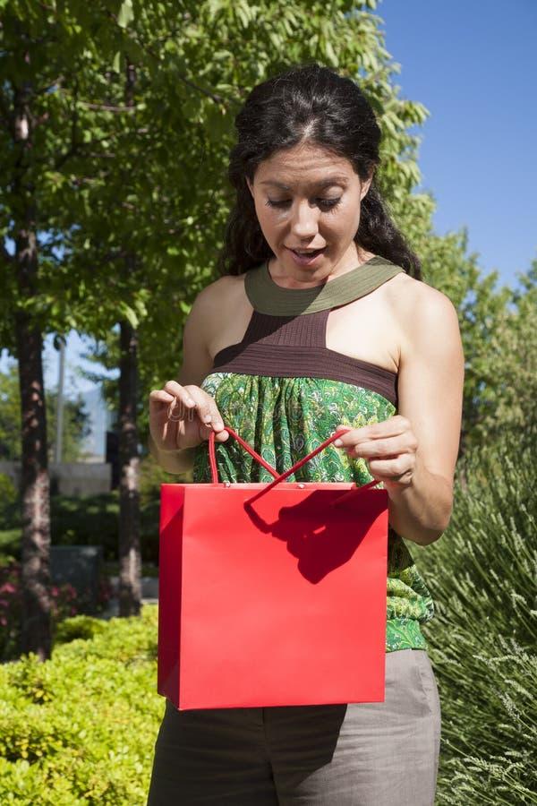 Überraschte glückliche Frau mit Einkaufstasche lizenzfreie stockfotografie