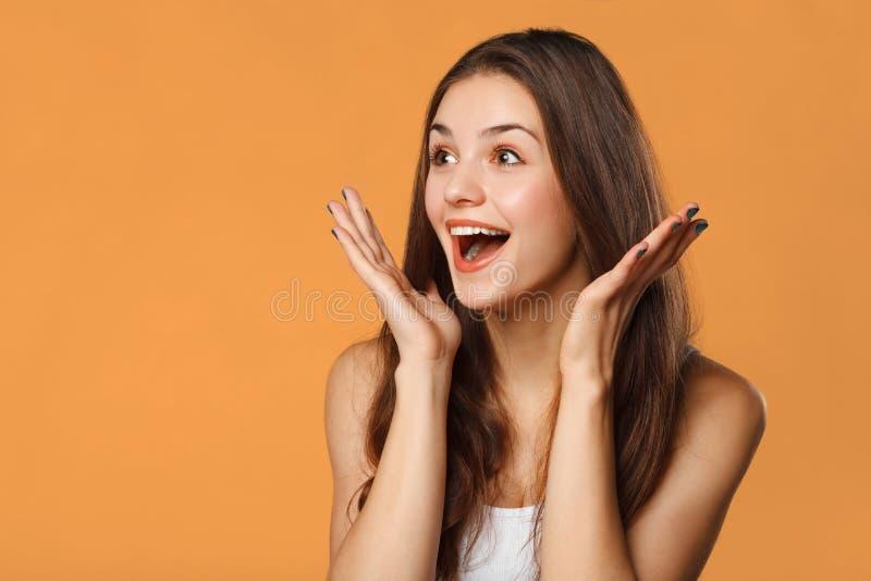 Überraschte glückliche Schönheit, die seitlich in der Aufregung schaut Lokalisiert auf orange Hintergrund stockfoto