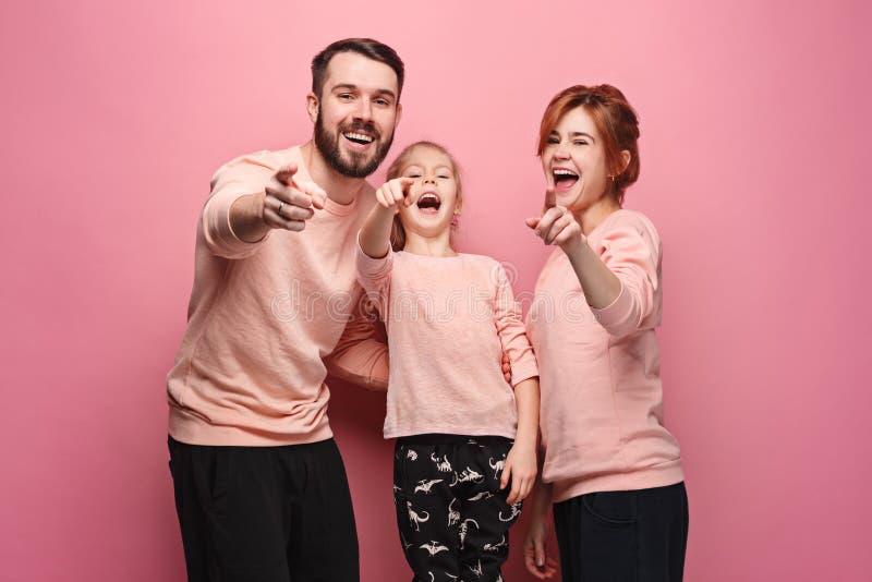 Überraschte junge Familie auf Rosa lizenzfreie stockfotografie