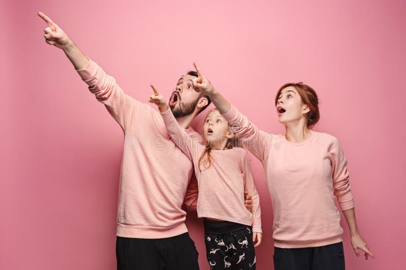 Überraschte junge Familie auf Rosa stockfotografie
