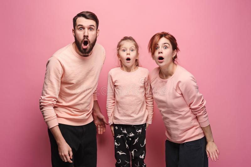 Überraschte junge Familie, die Kamera auf Rosa betrachtet lizenzfreie stockfotos