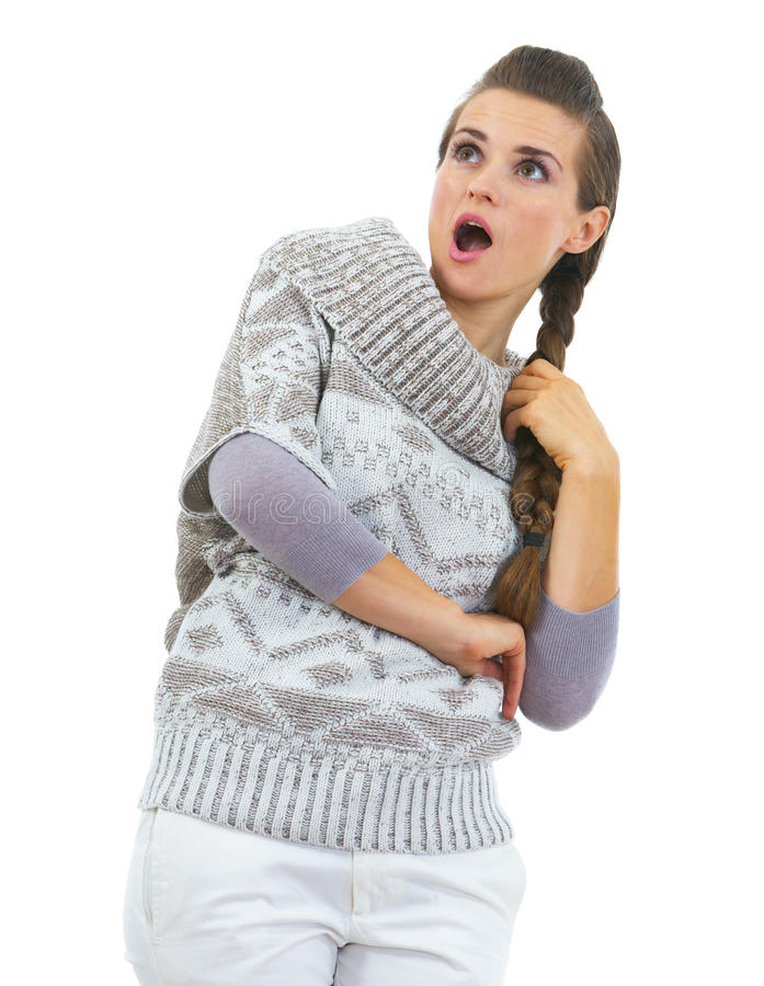 Überraschte junge Frau in der Strickjacke, die auf Kopienraum schaut stockfotos