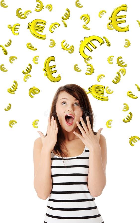 Überraschte junge Frau, die auf unten fallen Euro schaut stockfotos