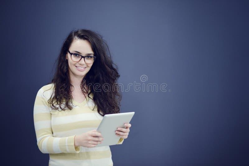 Überraschte junge Frau, die eine digitale Tablette halten verwendet stockbild