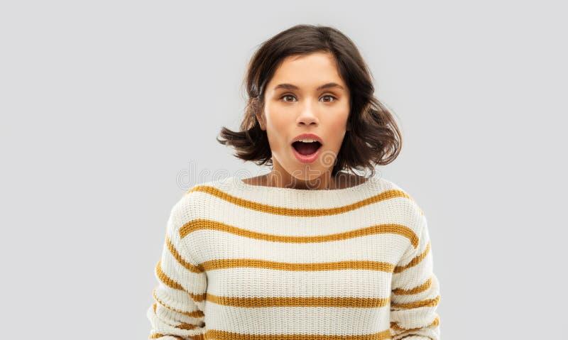 Überraschte junge Frau in gestreiftem Pullover lizenzfreies stockfoto