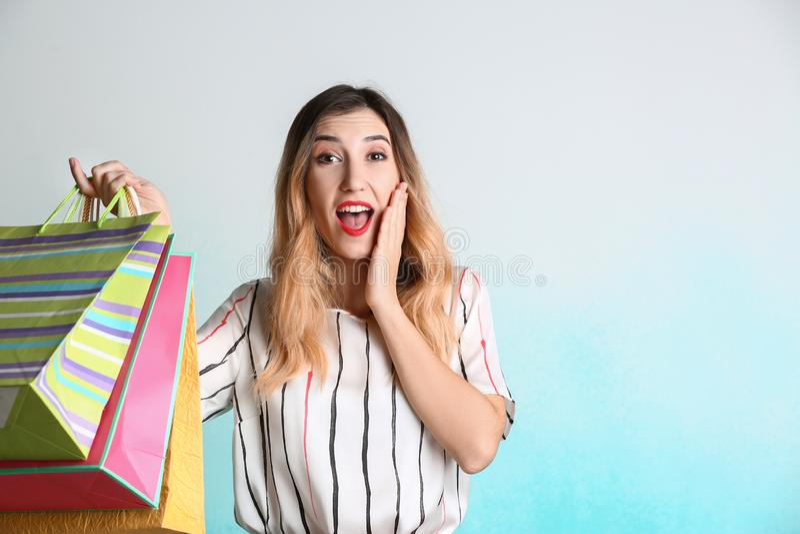Überraschte junge Frau mit Einkaufstaschen auf hellem Hintergrund lizenzfreies stockbild