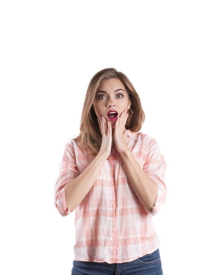 Überraschte junge Frau mit Haarstellung und -bedeckung ihr Mund mit den Händen, lokalisiert auf weißem Hintergrund stockfoto