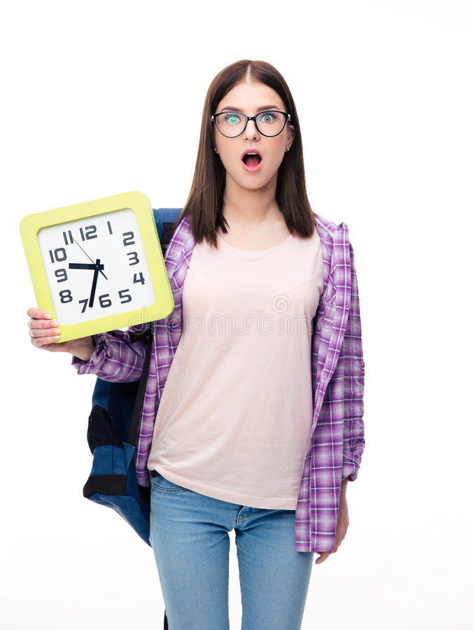 Überraschte junge Studentin, die große Uhr hält stockbilder