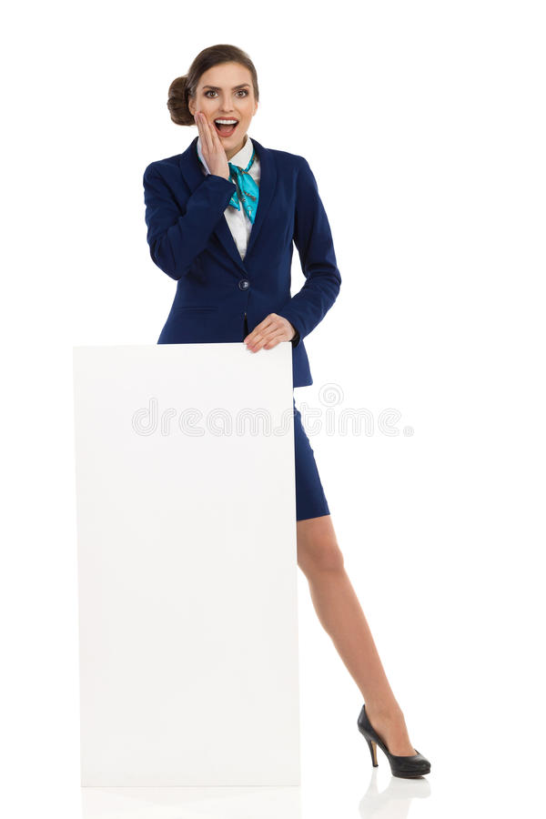 Überraschte Kabinen-Mannschafts-Frau, die hinter Plakat steht lizenzfreie stockfotos