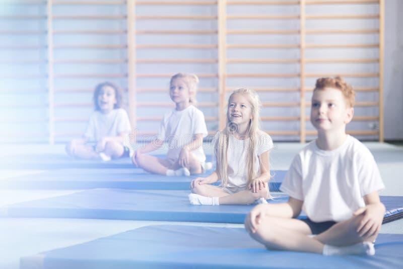 Überraschte Kinder in den Yogaklassen lizenzfreies stockbild