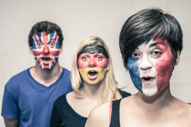 Überraschte Leute mit europäischen Flaggen auf Gesichtern lizenzfreie stockfotografie