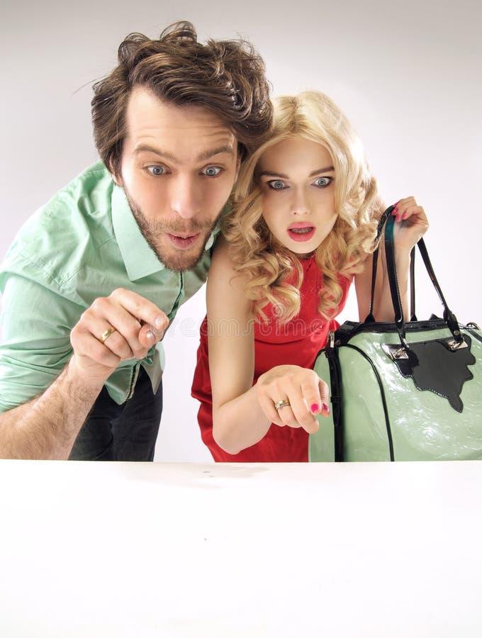 Überraschte Paare, die entlang der Verkäufe anstarren stockbild