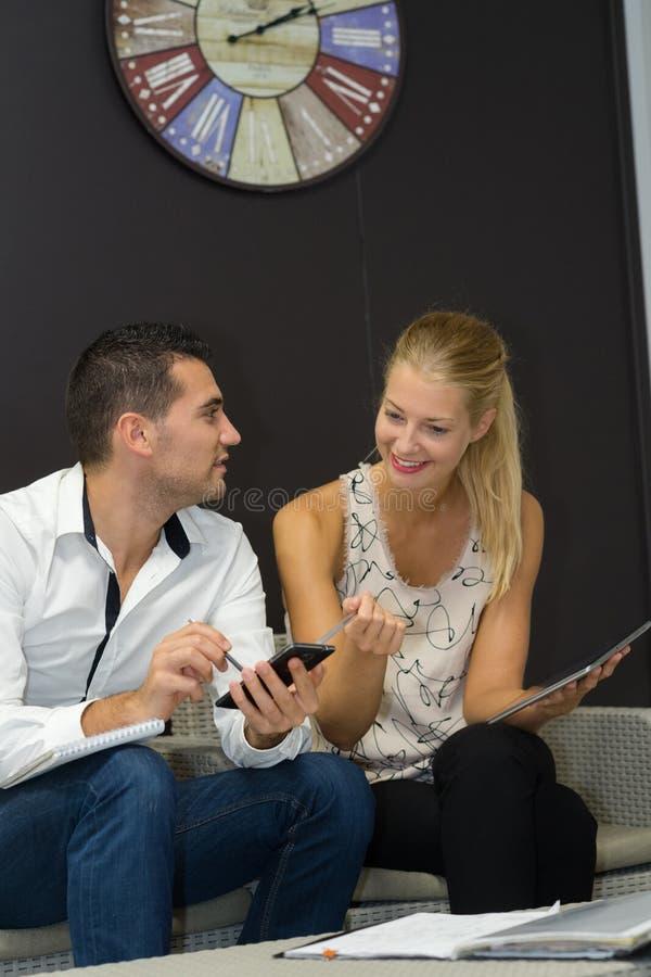 Überraschte Paare, die ihre Konten im Wohnzimmer tun lizenzfreies stockbild