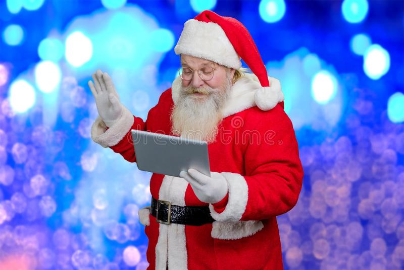 Überraschte Santa Claus mit PC-Tablette stockbilder