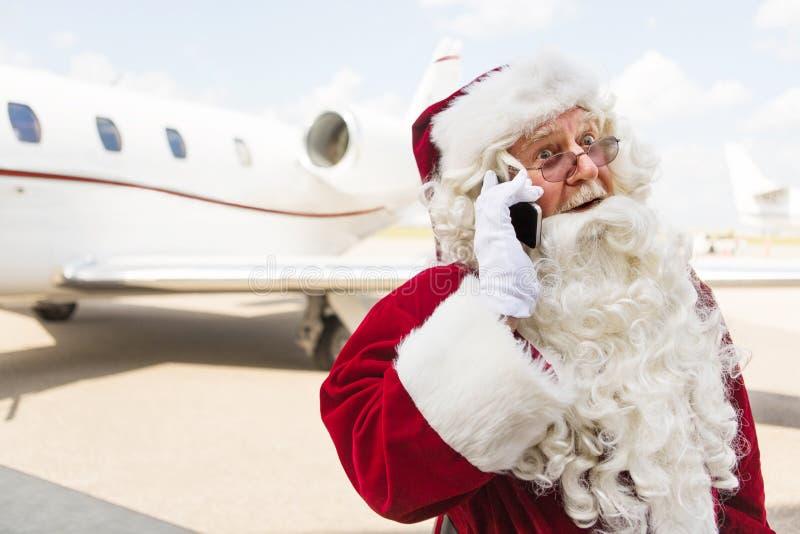 Überraschte Santa Using Mobile Phone Against privat stockfoto