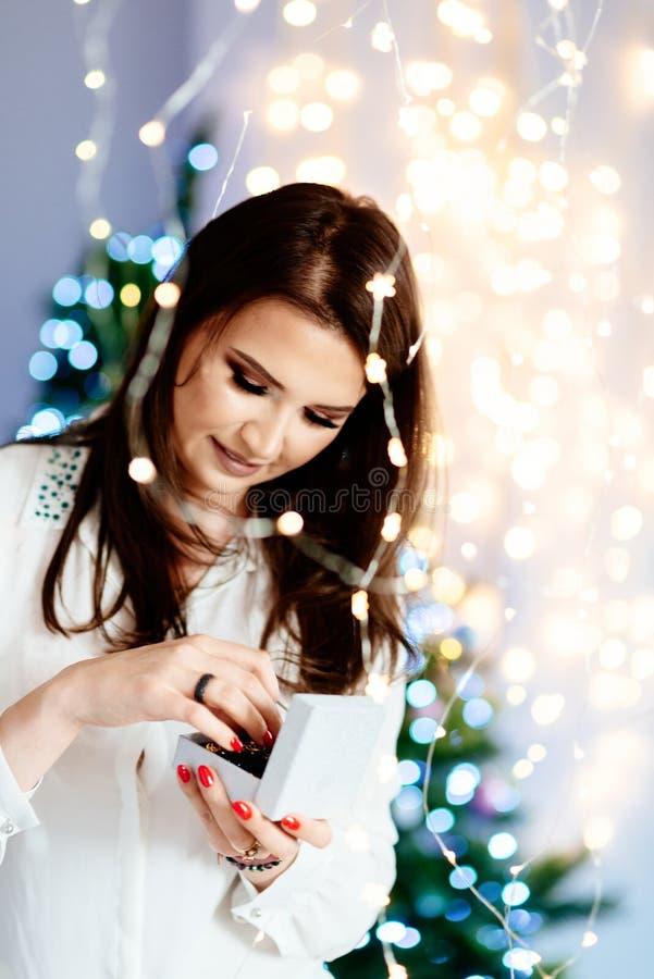 Überraschte schöne junge Frau, die eine offene Schmuckgeschenkbox hält lizenzfreies stockfoto