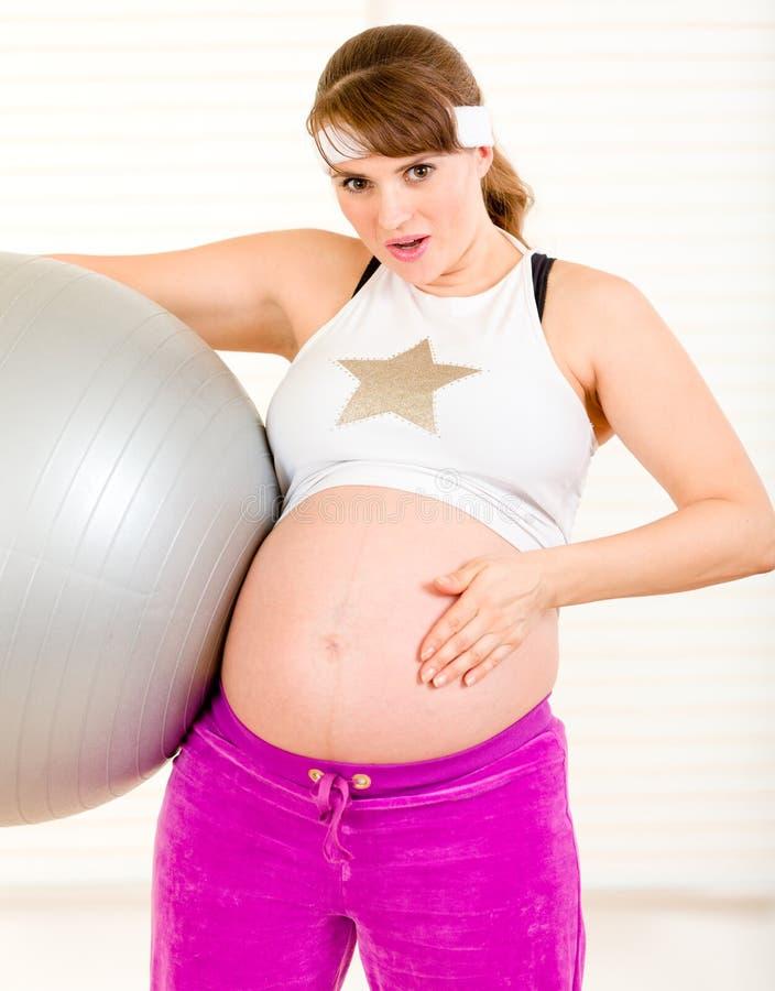 Überraschte schwangere Frau, die ihren Bauch berührt stockfoto