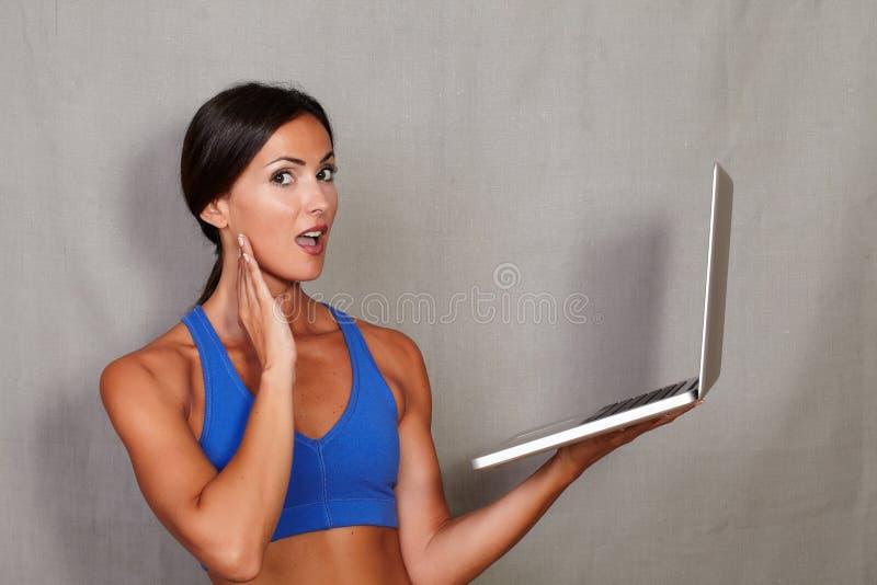 Überraschte tragende Laptop-Computer der erwachsenen Frau stockbild