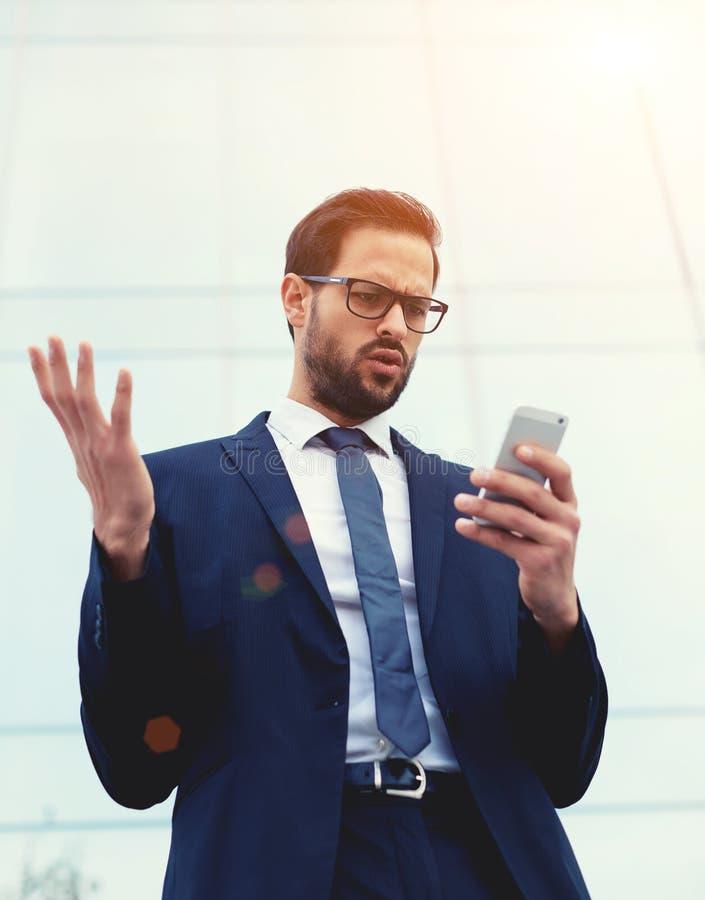 Überraschte und entsetzte Exekutive, die das intelligente Telefon empfängt schlechte Nachrichten betrachtet lizenzfreies stockfoto