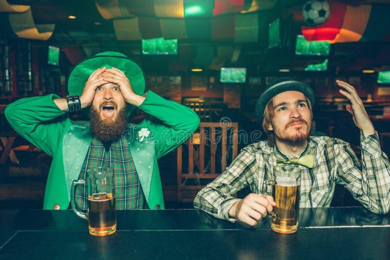 Überraschte und umgekippte junge Männer sitzen am Barzähler in der Kneipe Sie passen oben vorwärts und Beifall auf Kerle unglückl stockfotografie