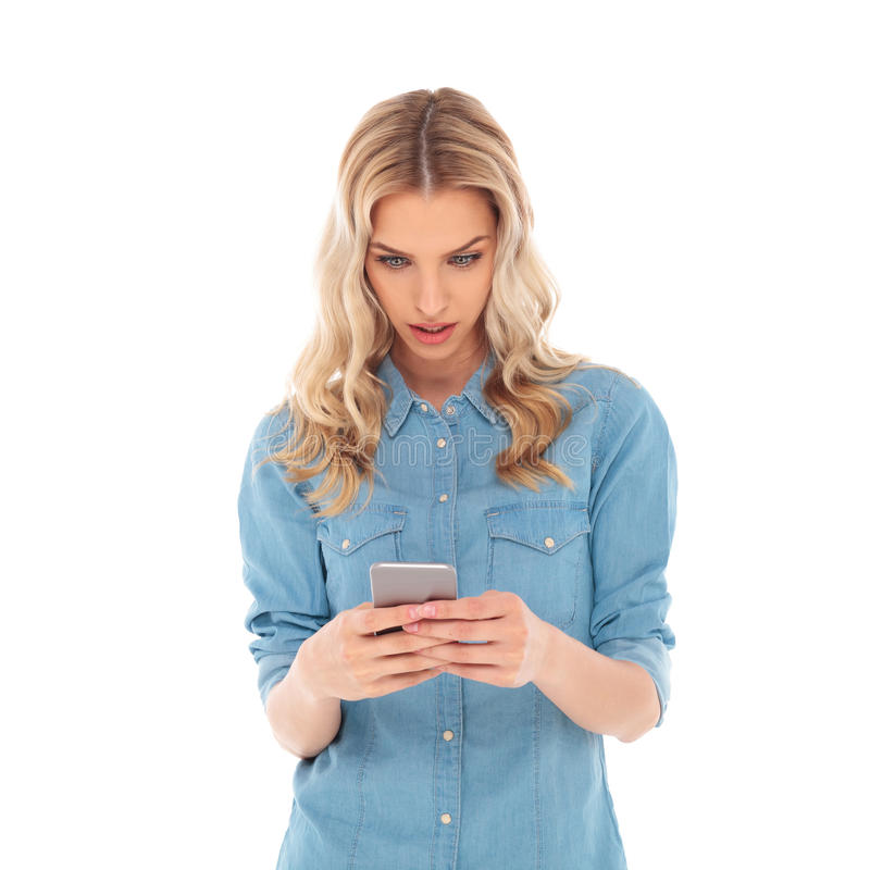 Überraschte zufällige Blondine, die auf ihrem Smartphone simsen stockbilder