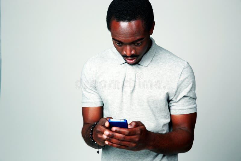 Überraschter afrikanischer Mann, der Smartphone verwendet lizenzfreie stockfotos