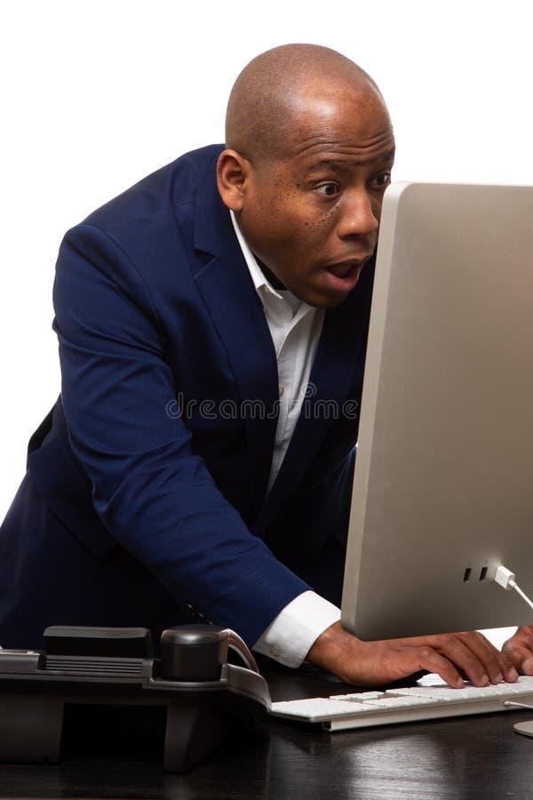 Überraschter Afroamerikaner-Geschäftsmann Looks At Computer stockfoto
