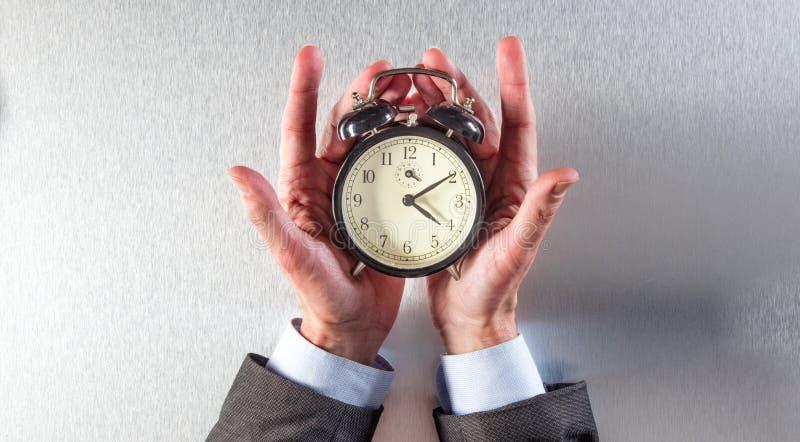 Überraschter Geschäftsmann übergibt das Halten eines Weckers für Zeitstrategie lizenzfreies stockbild