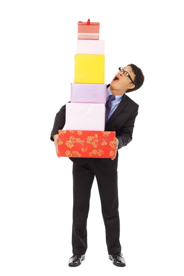Überraschter Geschäftsmann, der Geschenkboxen hält Lokalisiert auf weißem BAC lizenzfreies stockfoto